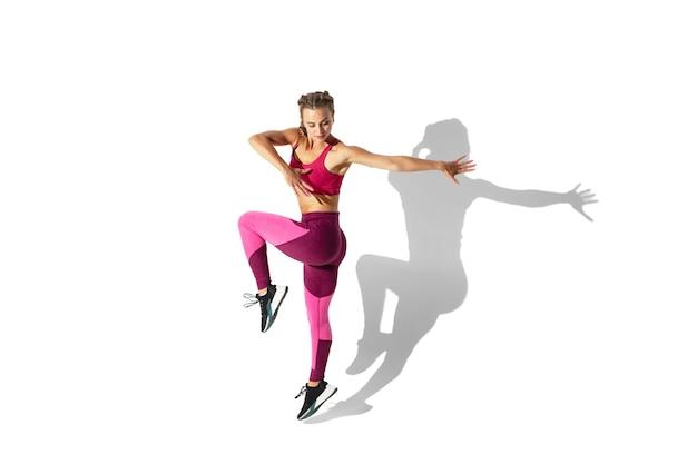 Bela jovem atleta praticando na parede branca do estúdio com sombras
