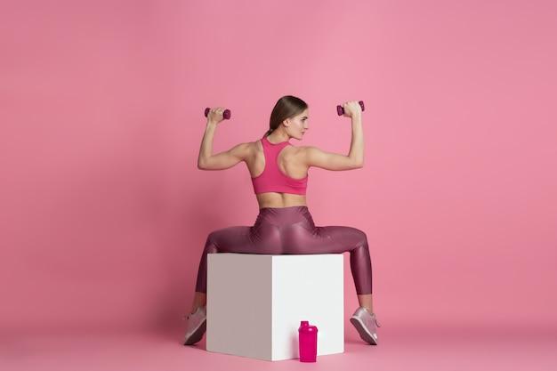 Bela jovem atleta praticando no estúdio rosa