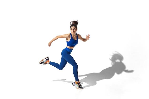 Bela jovem atleta praticando no fundo branco do estúdio com sombras