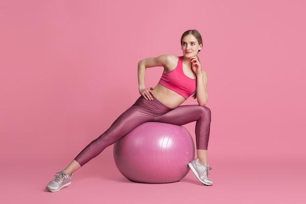 Bela jovem atleta praticando no retrato monocromático de parede rosa