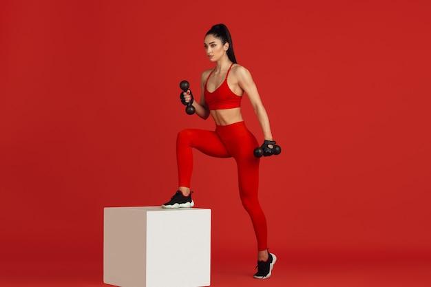 Bela jovem atleta praticando no retrato monocromático de parede vermelha