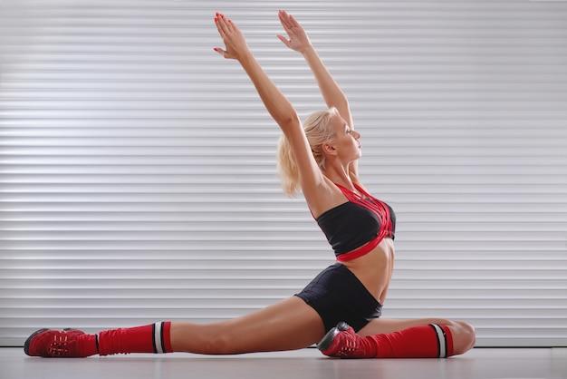 Bela jovem atlética alongamento antes de treino