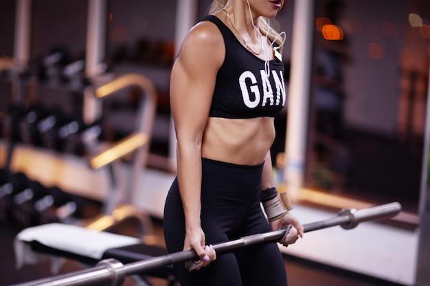 Bela jovem atlética está treinando no ginásio