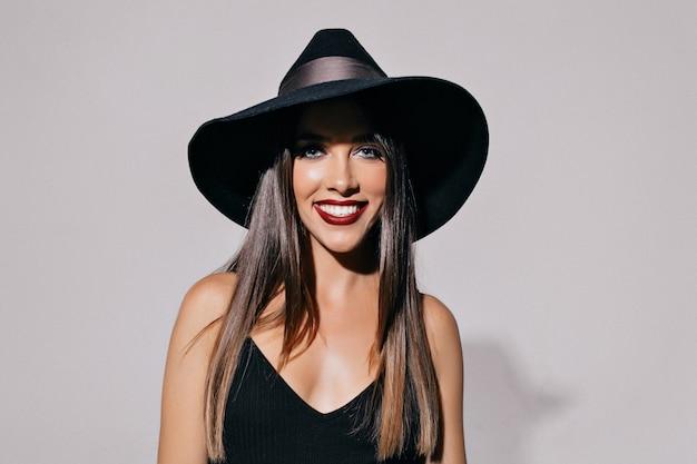 Bela jovem atraente com olhos esfumaçados e lábios negros, usando chapéu e vestido preto, posando de frente para a parede. halloween, baile de máscaras, festa, celebração