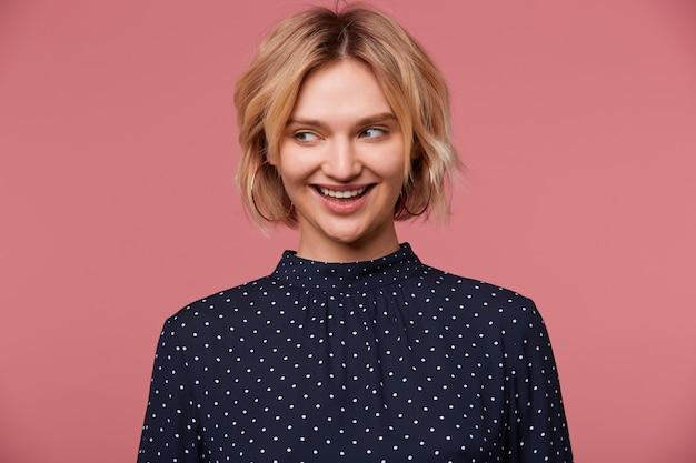 Bela jovem atraente loira vestida com blusa com bolinhas, tem expressão facial alegre, sorrindo, falando coquete olhando para o lado, isolado