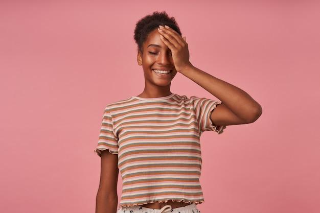 Bela jovem atraente morena encaracolada com a palma da mão levantada no rosto enquanto ri alegremente com os olhos fechados, posando sobre uma parede rosa