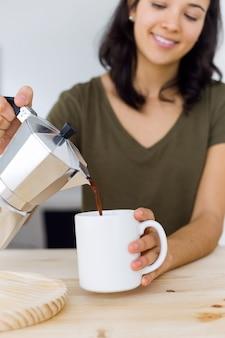 Bela jovem bebendo café em casa.