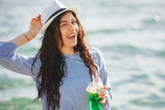 Bela jovem bebendo cocktail na praia. garota atraente, oferecendo uma bebida. linda mulher bebendo limonada