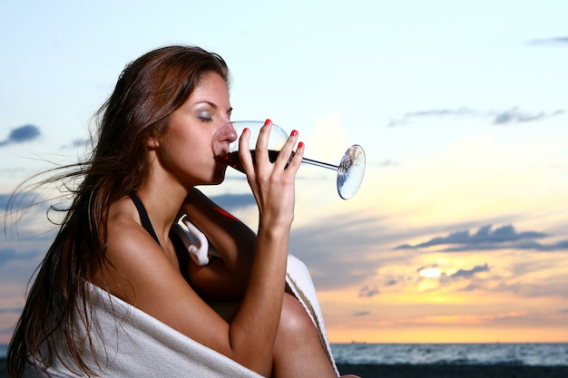 Bela jovem bebendo vinho na praia