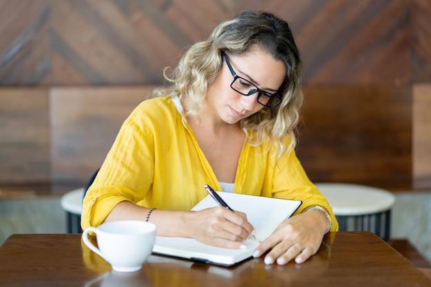Bela jovem beber café e escrever planos para o dia