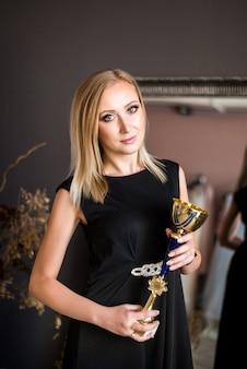 Bela jovem bem sucedida mulher loira com taça de ouro