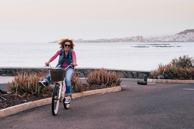 Bela jovem bonita com cabelo encaracolado ao vento se movia com uma bicicleta