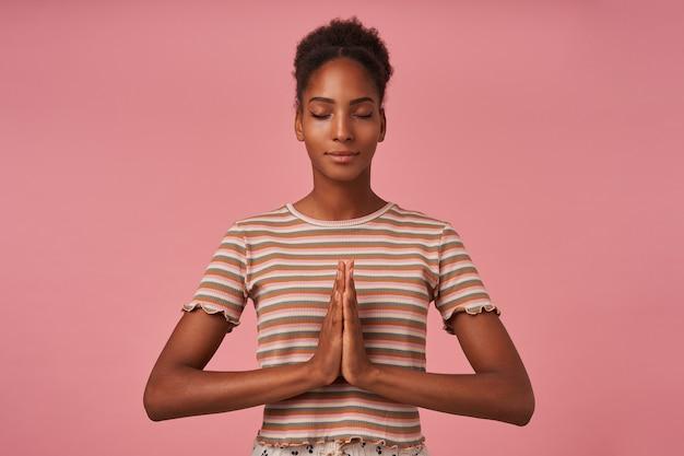 Bela jovem bonita de cabelos castanhos cacheados com coque, cruzando as mãos enquanto medita com os olhos fechados, isolado sobre a parede rosa
