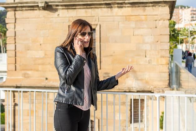 Bela jovem brava falando no celular em málaga, um dia ensolarado