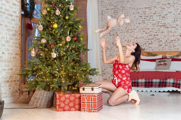 Bela jovem brincando com um ursinho de pelúcia na árvore de natal