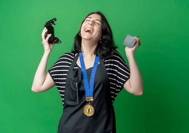 Bela jovem cabeleireira com avental com medalha de ouro no pescoço segurando troféu e spray rindo feliz e animada em pé sobre a parede verde