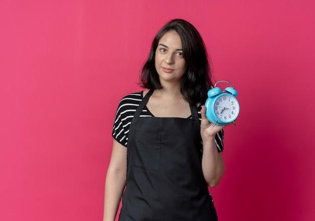 Bela jovem cabeleireira com avental mostrando despertador com expressão confiante em pé sobre a parede rosa