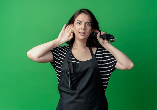Bela jovem cabeleireira com avental segurando a mão perto da orelha tentando ouvir fofoca sobre o verde