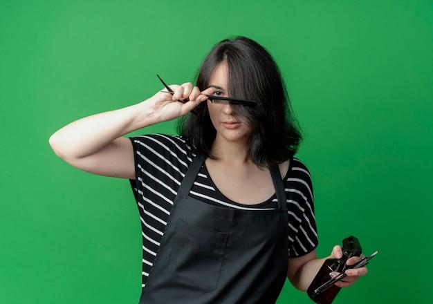Bela jovem cabeleireira com avental segurando o pente e a navalha sorrindo confiante sobre o verde