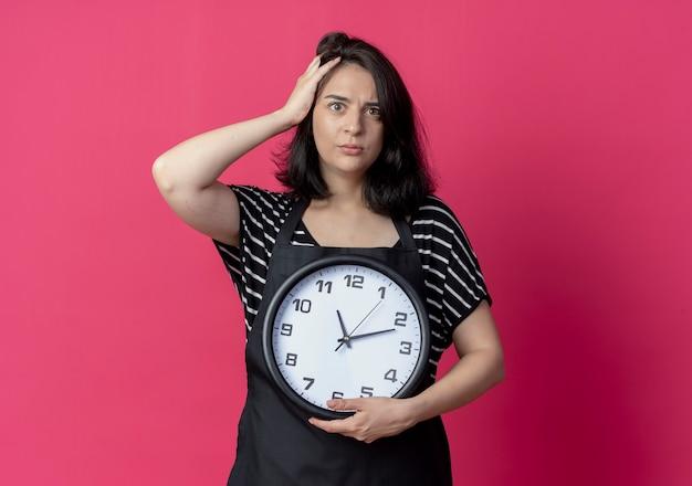 Bela jovem cabeleireira com avental segurando o relógio de parede com a mão na cabeça por engano, parecendo estar confusa sobre rosa