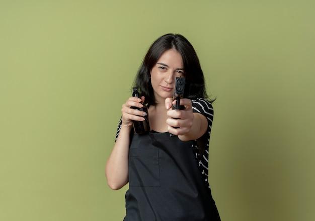 Bela jovem cabeleireira com avental segurando spray e apontando a arma com cara séria em pé sobre a parede de luz