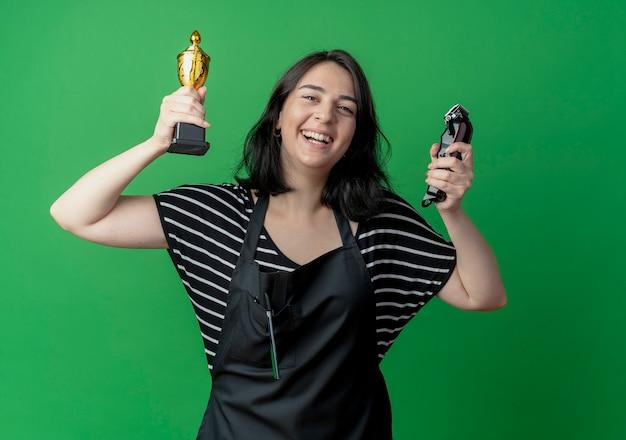Bela jovem cabeleireira com avental segurando troféu e aparador feliz e animada, regozijando-se com seu sucesso sobre o verde