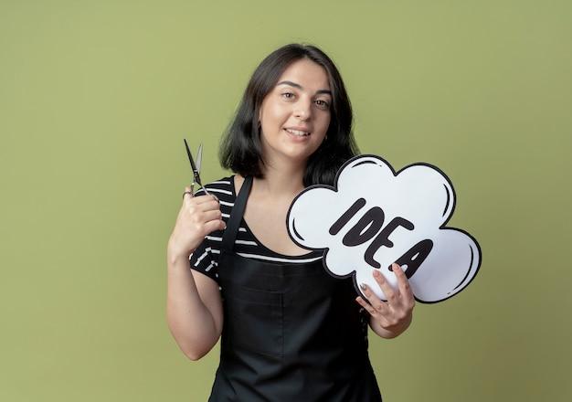 Bela jovem cabeleireira com avental segurando uma tesoura e um balão de fala em branco com a palavra ideia sorrindo em pé sobre a parede de luz