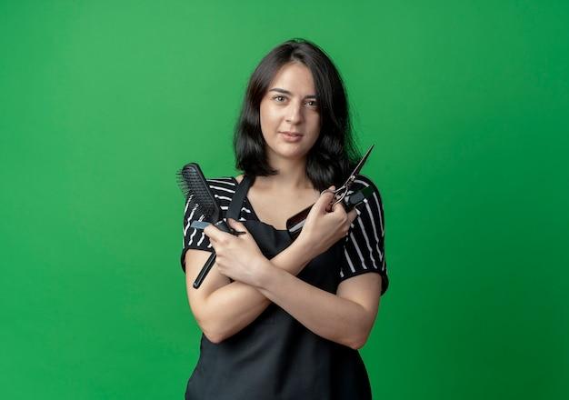 Bela jovem cabeleireira com avental segurando uma tesoura spray e pincel com um sorriso confiante cruzando as mãos sobre o verde