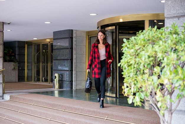 Bela jovem caminhando deixando um hotel vestindo roupas elegantes de outono