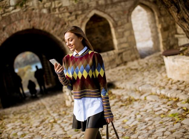 Bela jovem caminhando no parque outono e usando um telefone celular