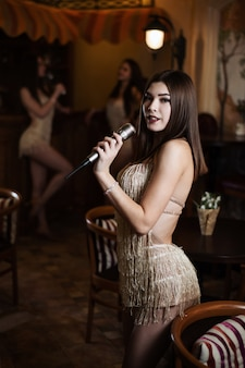 Bela jovem cantando músicas de karaokê no microfone em um restaurante