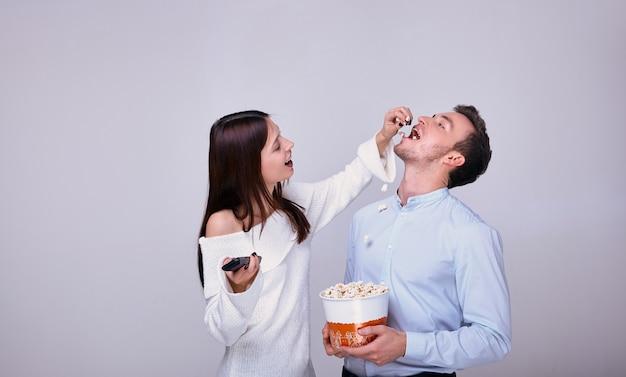 Bela jovem casal apaixonado, assistindo filme e comendo pipoca