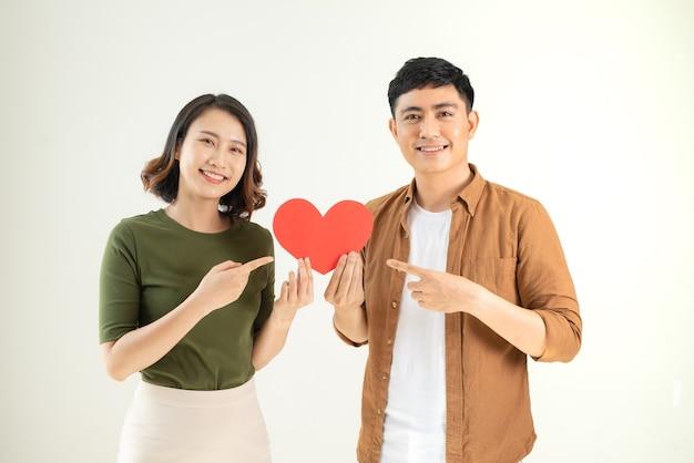 Bela jovem casal apaixonado está segurando um cartão em forma de coração, sobre uma parede branca.