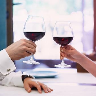 Bela jovem casal com copos de vinho tinto no restaurante de luxo