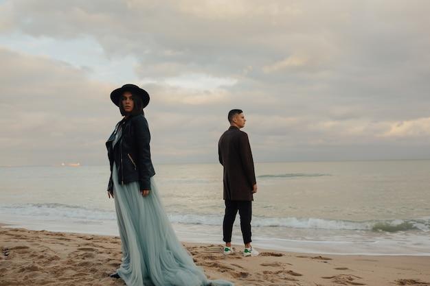 Bela jovem casal de noivos na costa com céu nublado no fundo.