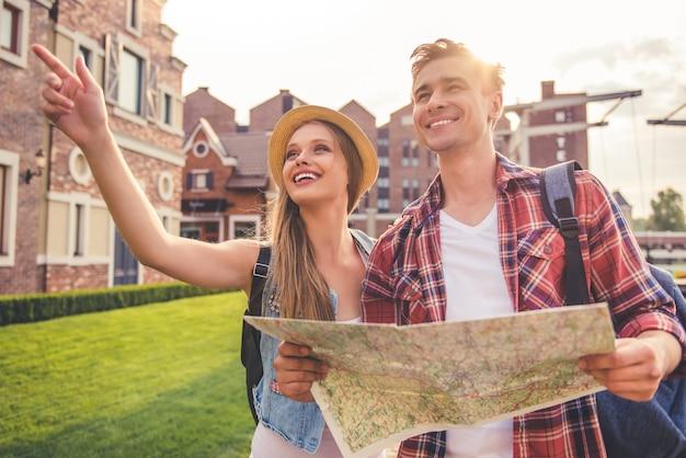 Bela jovem casal de viajantes está usando um mapa.