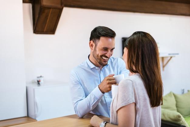 Bela jovem casal está conversando e sorrindo enquanto bebe café