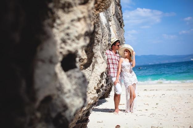 Bela jovem casal feliz na praia, afago contra o mar e as montanhas