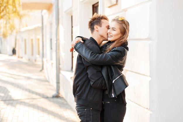 Bela jovem casal feliz se beijando na cidade em um dia ensolarado