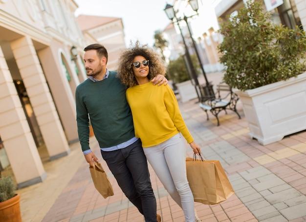 Bela jovem casal multiétnico, desfrutando de compras, se divertindo na cidade
