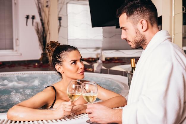 Bela jovem casal relaxando juntos e bebendo vinho branco no spa