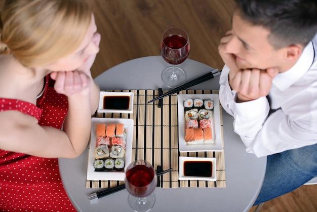 Bela jovem casal sentados juntos e comendo.