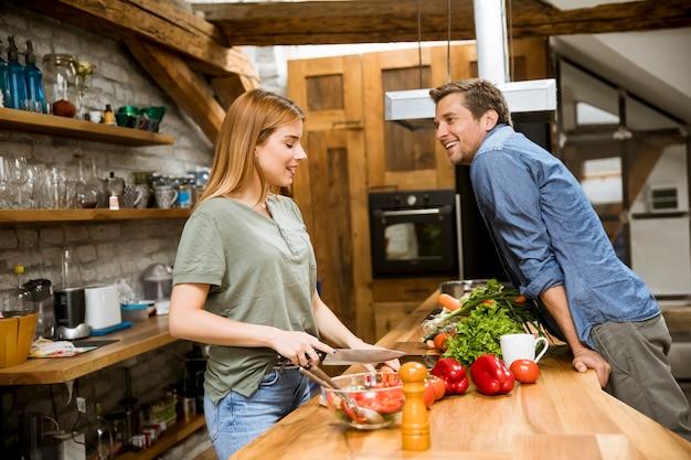 Bela jovem casal sorrindo enquanto cozinhando na cozinha em casa