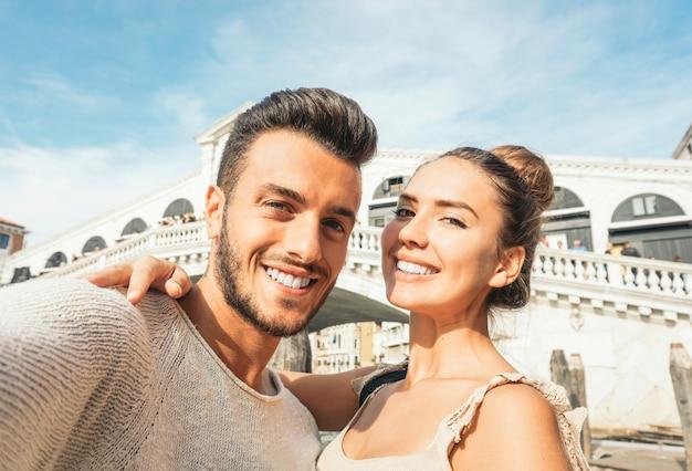Bela jovem casal tomando um selfie, aproveitando o tempo em sua viagem para veneza