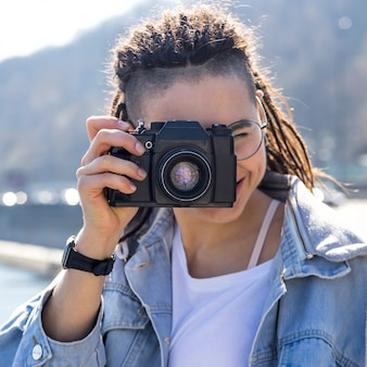 Bela jovem caucasiana com dreadlocks segurando uma câmera retro em suas mãos - fotografia como um hobby em viajar