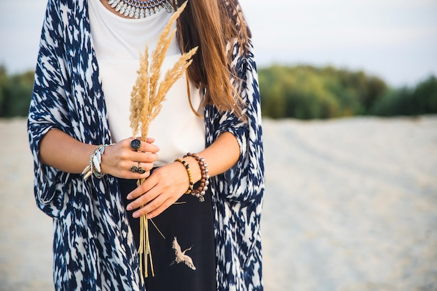 Bela jovem caucasiana em roupas no estilo de um boho com um monte de acessórios de anéis