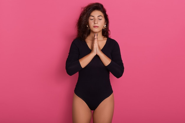 Bela jovem caucasiana fica em pose meditativa