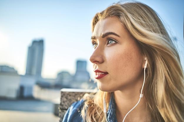 Bela jovem caucasiana ouvindo música com fones de ouvido