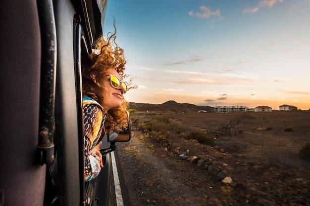 Bela jovem caucasiana viajar fora do carro com o vento nos cabelos cacheados, movimento e movimento na estrada descobrindo novos lugares durante um belo pôr do sol, desfrutar e o conceito de liberdade alegre