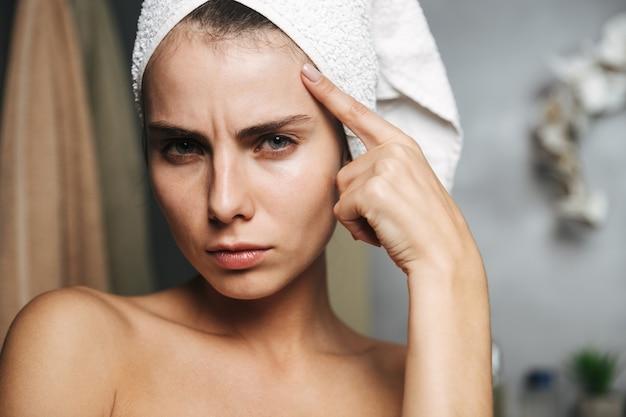 Bela jovem chateada enrolada em uma toalha de banho em pé no banheiro